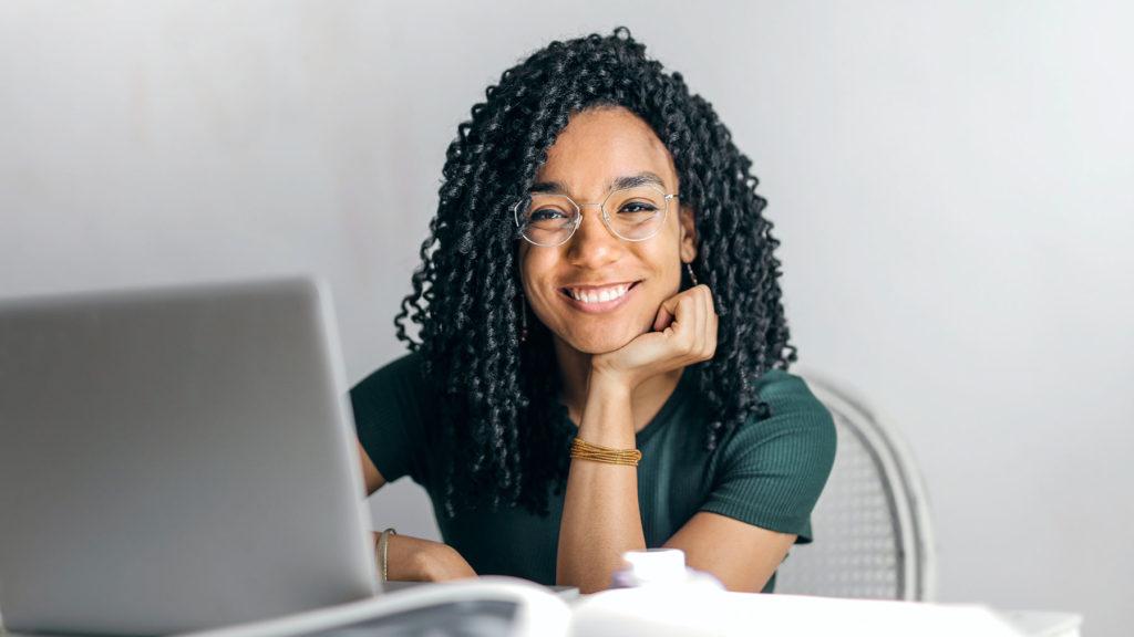 Person som sitter vid sin dator och ser glad ut