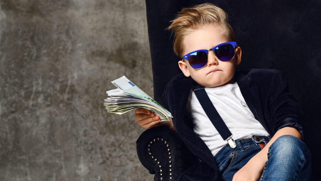 Pojke som sitter i en stol med mycket pengar