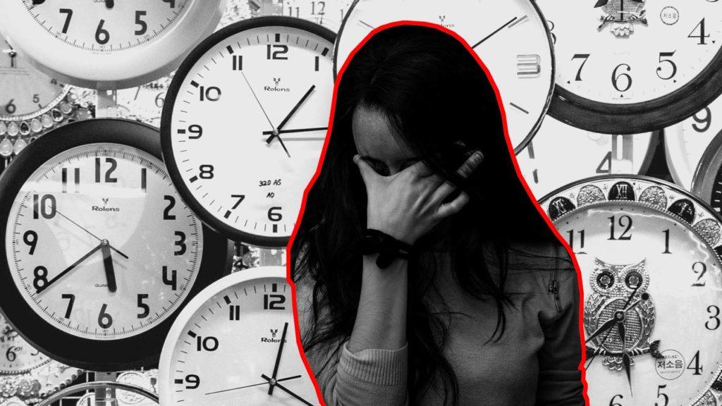 En person med långt hår som står framför en mängd klockor