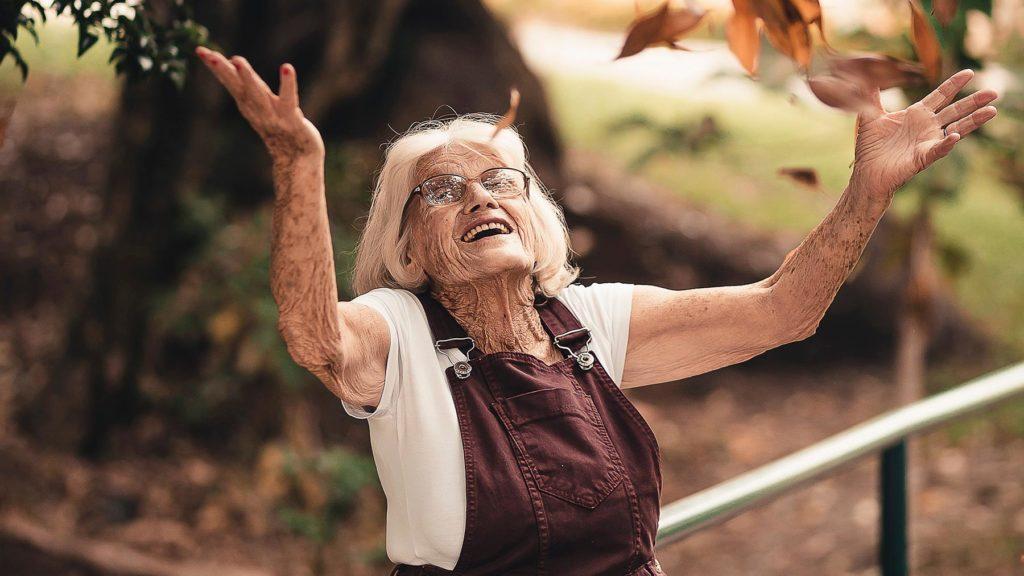 Kvinna med vitt hår som står i höstlöven