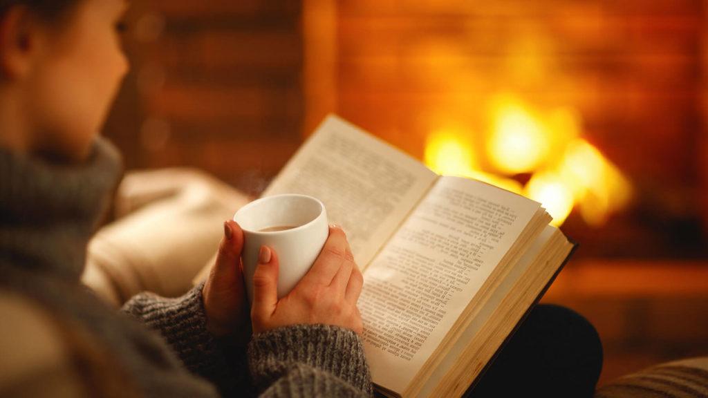 Kvinna läser bok framför öppna spisen.
