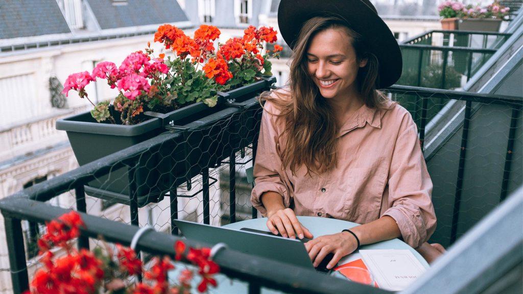 Person i rosa skjorta som jobbar på balkong med blommor