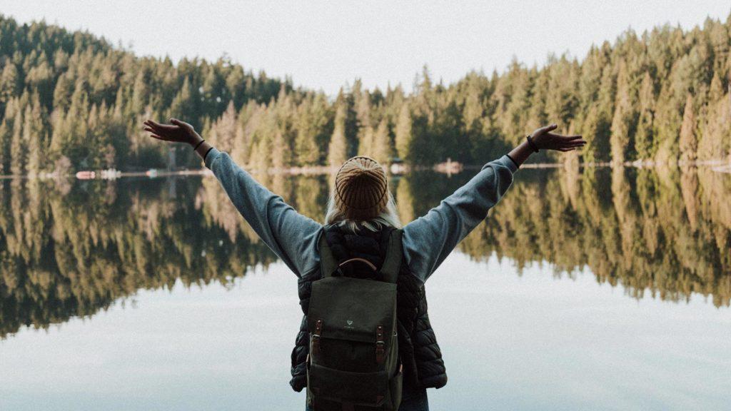 Person som står framför sjö och skog