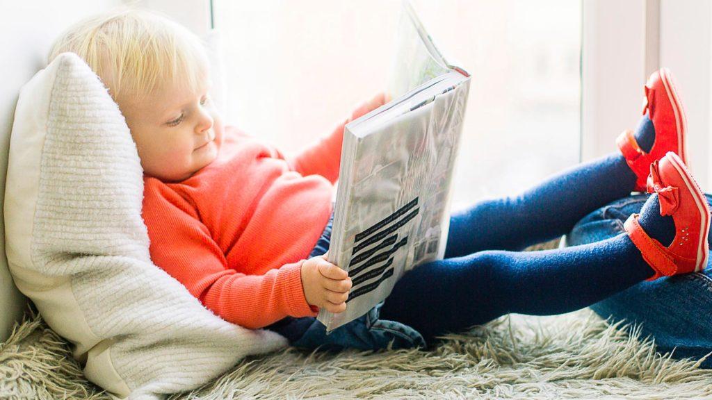 Ett barn i röd tröja som läser en bok