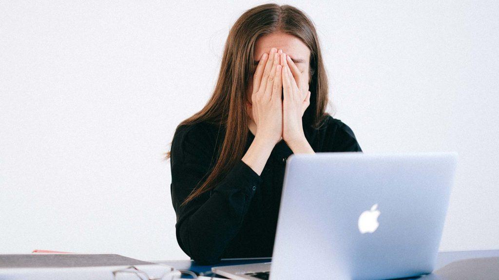 Person med laptop framför sig. Hon gömmer huvudet i händerna av stress