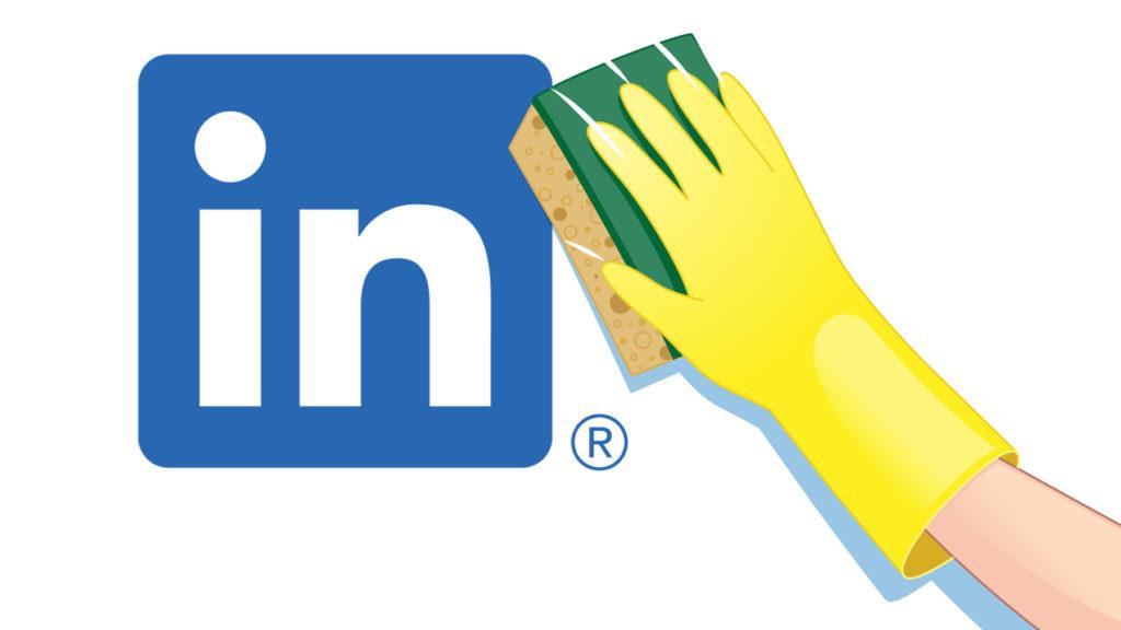 Hand med skursvamp tvättar av LinkedIns logotyp