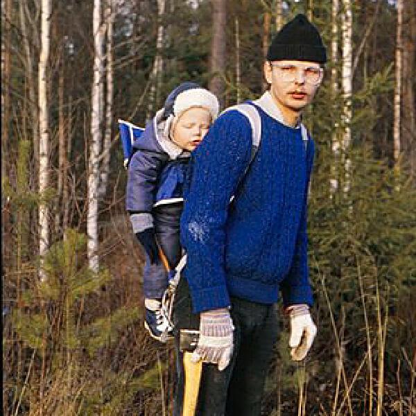 Rickard som barn på sin pappas rygg i skogen