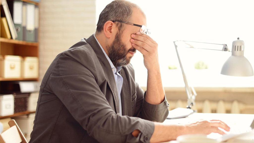 Trött chef som arbetar övertid vid sitt skrivbord