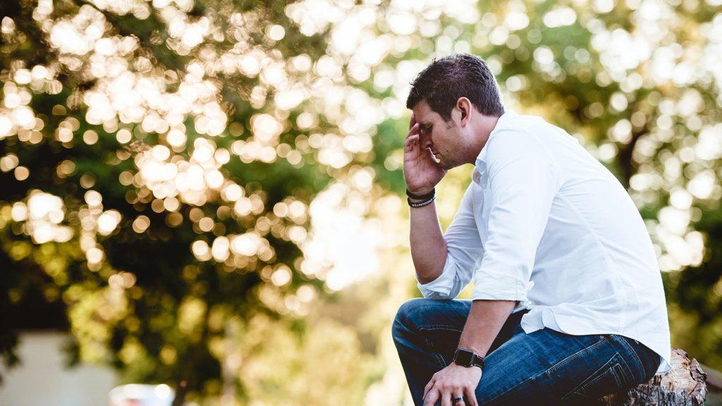 Utmattad man som sitter i en park
