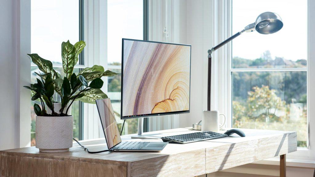 Hemmakontor med dator, lampa, kaffekopp, krukväxt oxh utsikt
