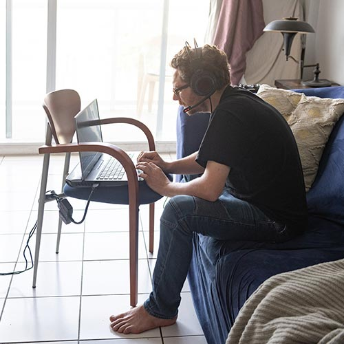 Person med dålig hållning som sitter på sitt hemmakontor med datorn på en stol