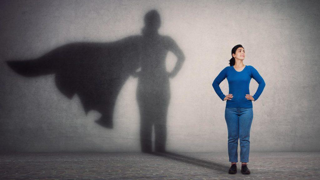 Kvinna i blått som har superhjälte-skugga