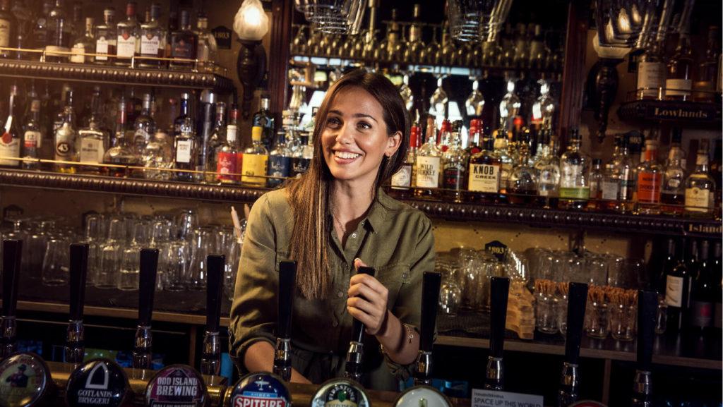 Foto på Jeny Meira som häller upp öl bakom en bardisk