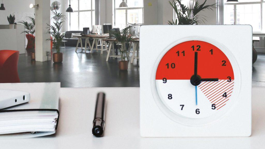 Klocka och arbetsplats med sex timmars arbetsdag