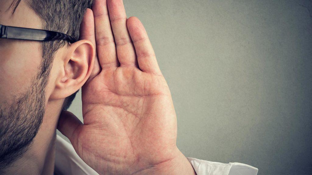Man som har handen bakom örat för att lyssna