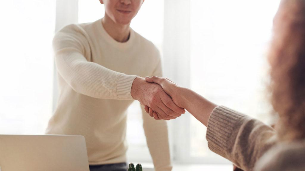 Två personer skakar hand efter lönesamtal
