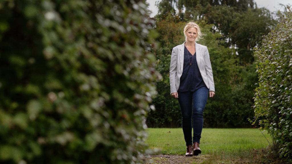 Jessica Alfredson i helfigur går på en gräsmatta.