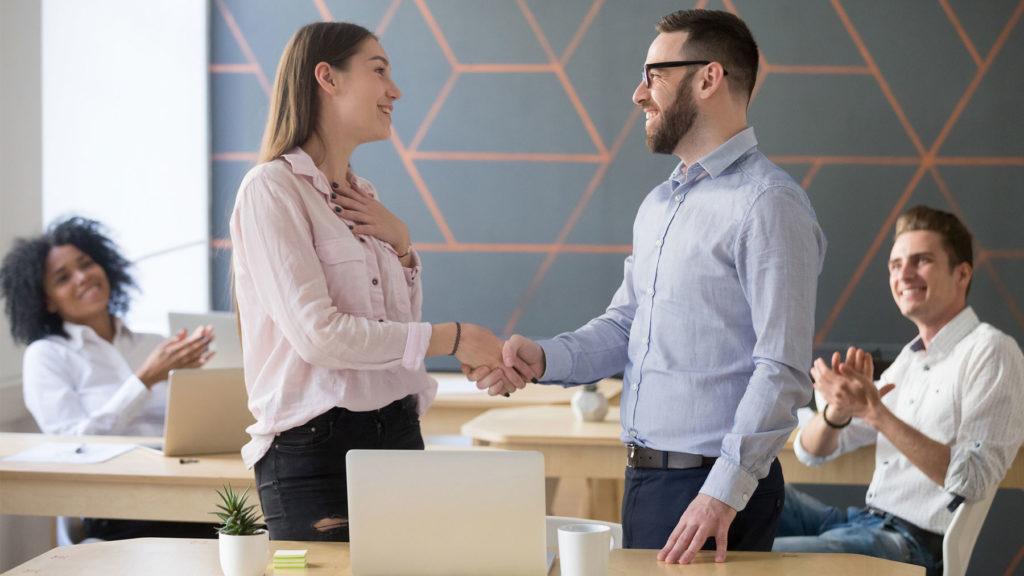 Person som blir tackad av chefen inför kollegor