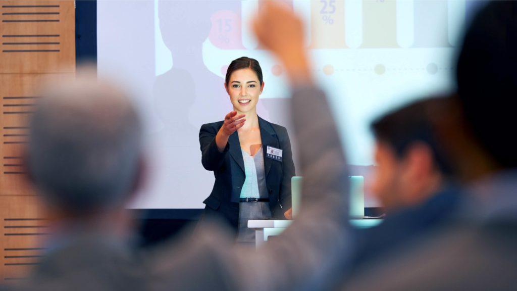 Ung kvinna som talar inför publik.