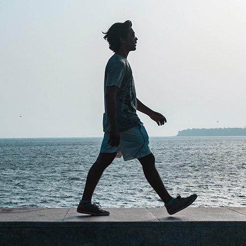 Person som promenerar vid vatten