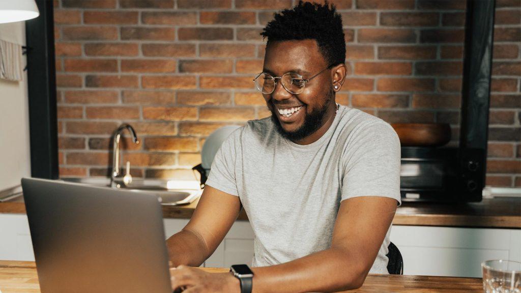 Person i grå tröja som är ny på jobbet och jobbar hemifrån vid sin dator