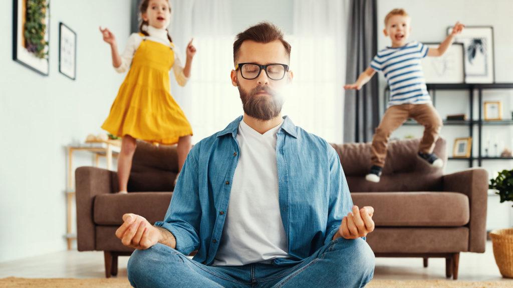 Man som mediterar med barn i bakgrunden