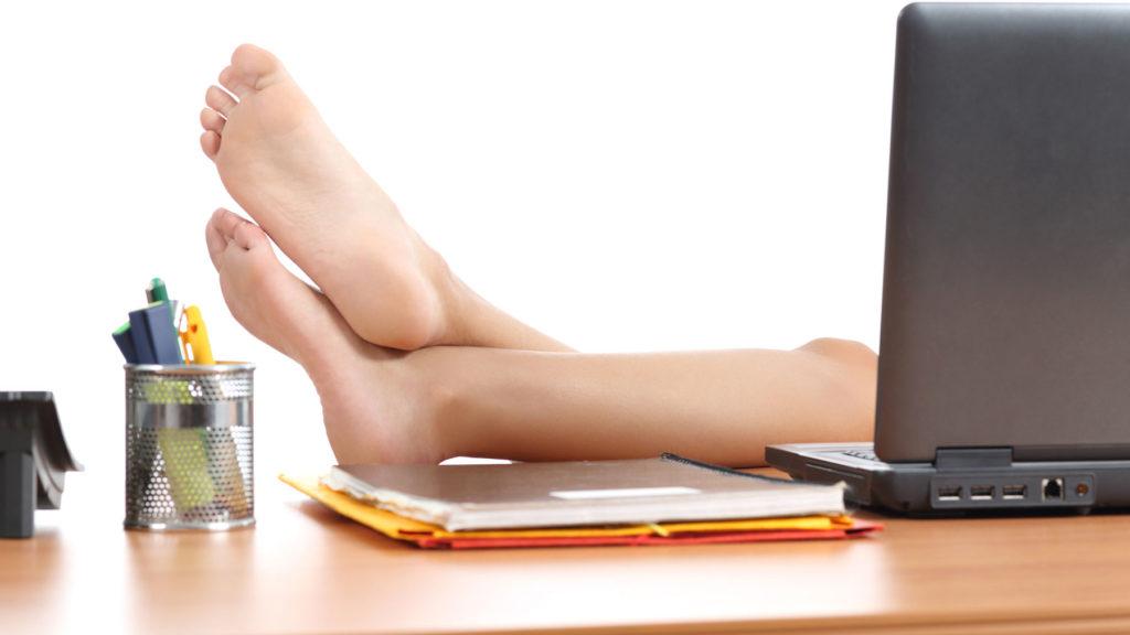 Nakna ben som sticker fram bakom en datorskärm