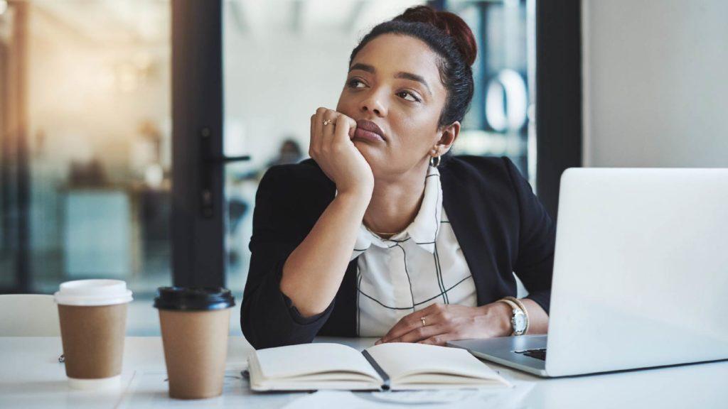Uttråkad kvinna framför laptop vid ett skrivbord.