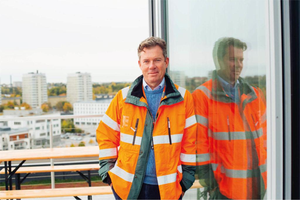 Porträttfoto av Anders Berge som står på en byggarbetsplats.