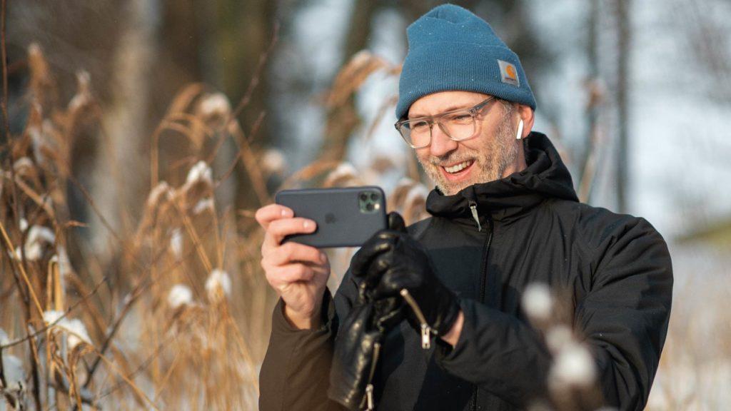 Anders Österlund står utomhus och pratar i en mobiltelefon.