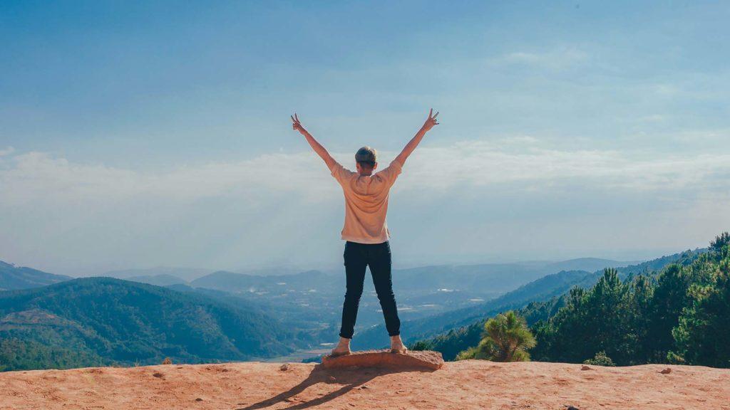Person som nått sitt mål, med armarna i vädret, upp mot himlen