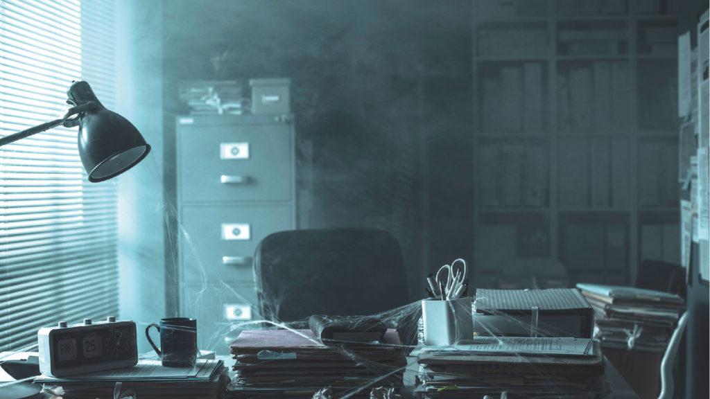 Fotografi med ett övergivet dammigt skrivbord på ett kontor.