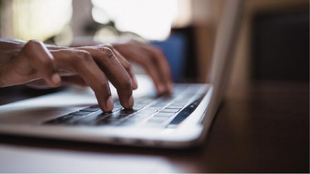 Fingrar som skriver på ett tangentbord.