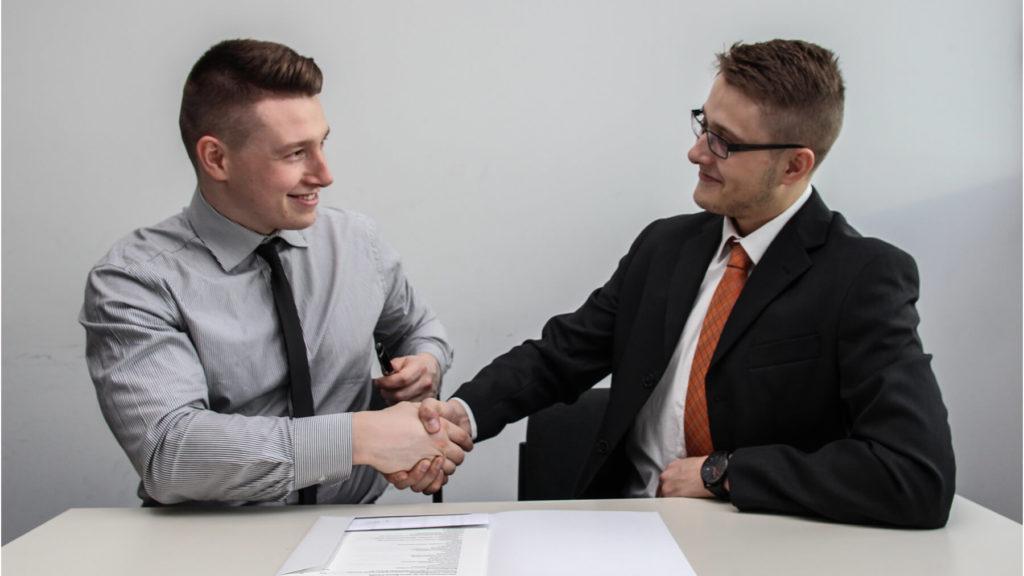 Två män sitter vid ett bord och skakar hand.