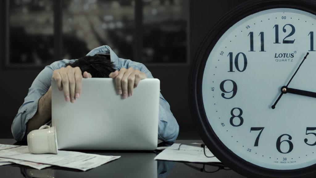 En person som ser mycket trött ut hänger över en dator. En klocka syns till höger i bilden.