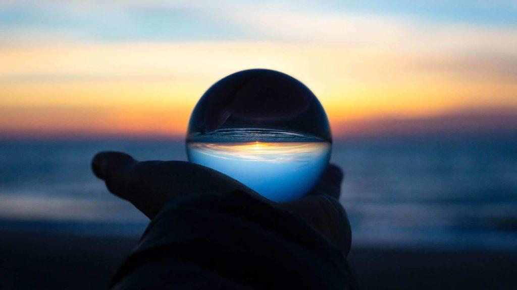 En hand håller upp vad som ser ut att vara en kristallkula. I bakgrunden en solnedgång.