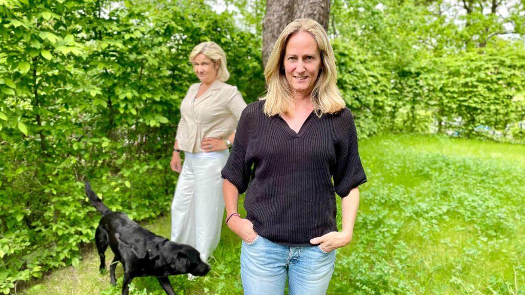 Katarina Ageborg i förgrunden och Cissi Elwin i bakgrunden. De står ute i en trädgård och vid Cissi står Katarinas svarta hund.