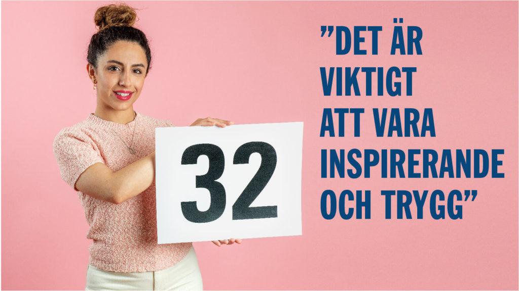 Helya Riazat håller upp en vit skylt med siffran 32.