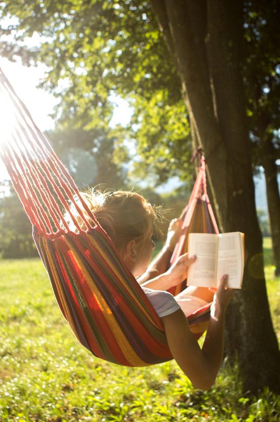 Bild på en person som ligger i en hängmatta och läser.
