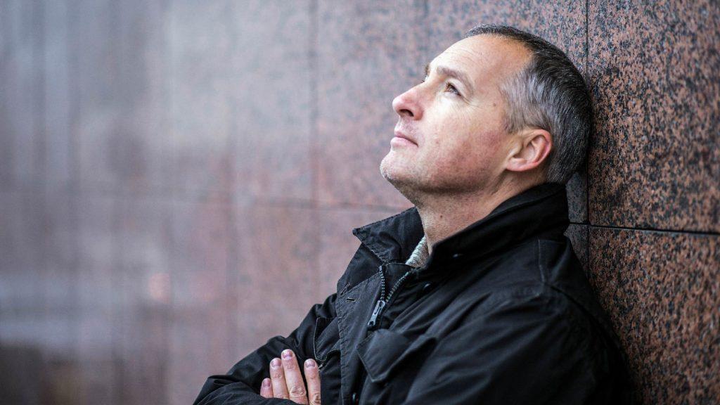 Foto på en bekymrad man som lutar sig mot en vägg.