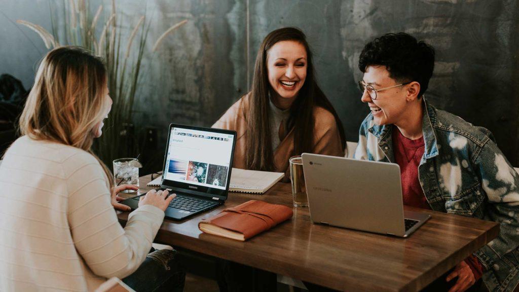 Tre kvinnor sitter framför sina datorer vid ett bord och pratar och skrattar.