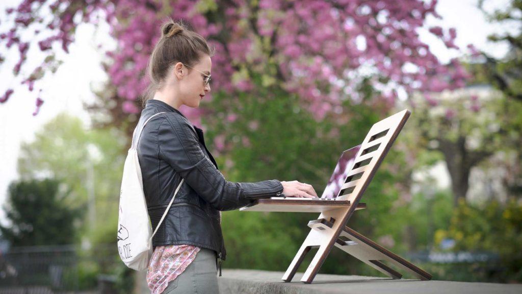 En ung kvinna står upp och jobbar utomhus med en dator framför sig.