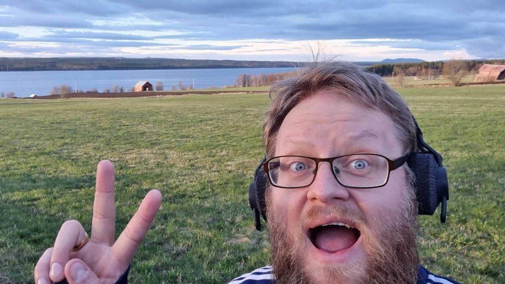 Cygnis medarbetare Thomas Dahlberg är ute på promenad i ett vackert, grönt landskap. Han gör v-tecknet och ler mot kameran.