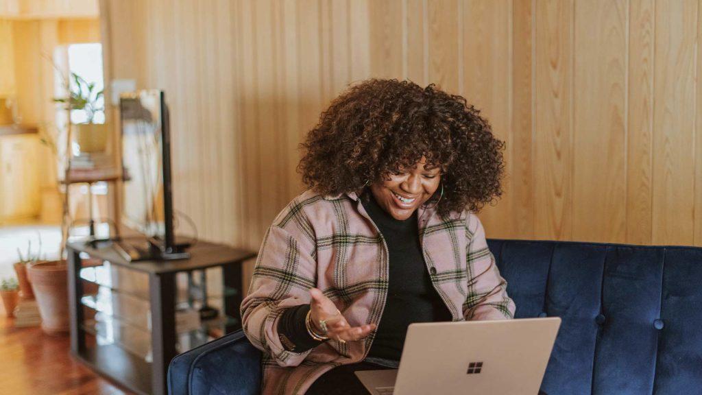 Kvinna sitter i en soffa med en dator i knäet.
