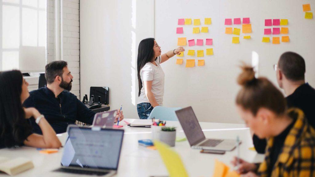 En kvinna står framför en Whiteboard-tavla med lappar på och talar inför en grupp personer som sitter vid ett bord.