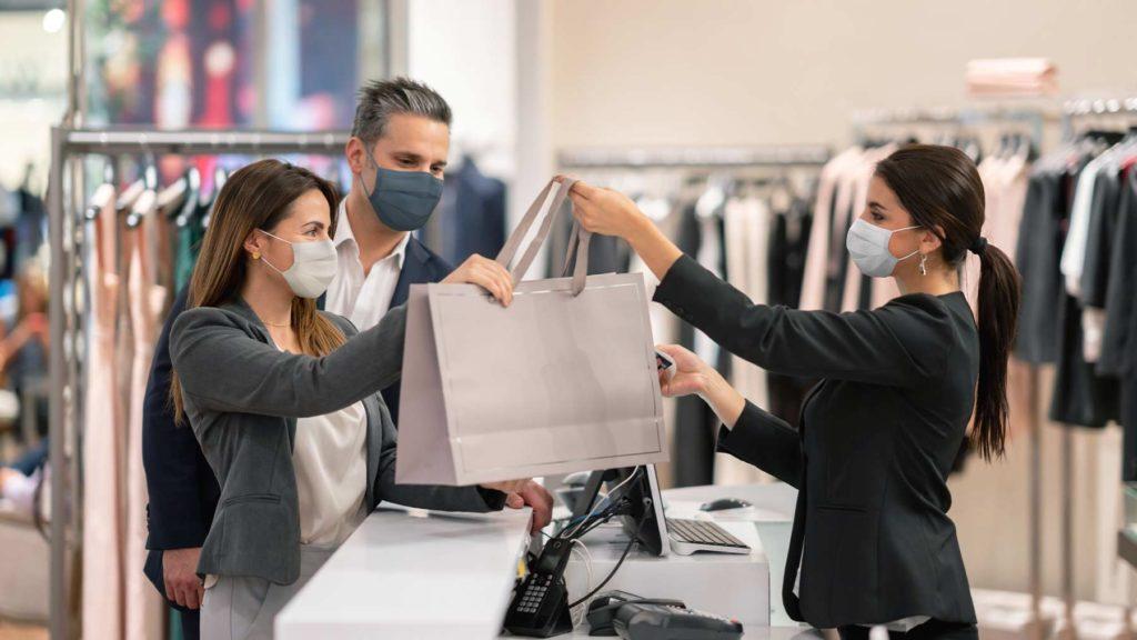 Ett butiksbiträde med munskydd överräcker en kasse till en man och en kvinna med munskydd. De står framme vid kassan.