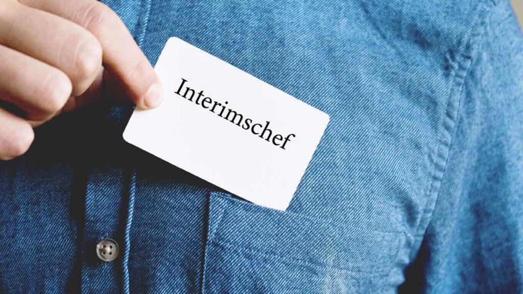 En hand håller upp en skylt som det står Interimschef på mot en jeansblus som bakgrund.