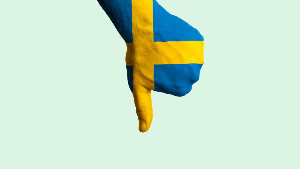 En hand i svenska flaggans färger som visar tummen ner.