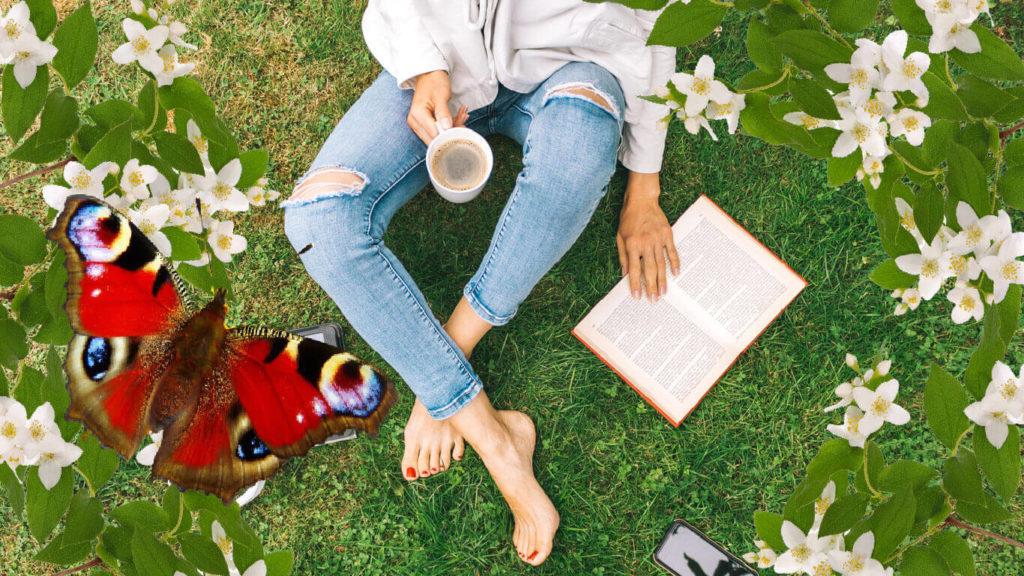En somrig bild på en person som sitter i gräset (man ser bara personens ben) med en kopp kaffe i en handen och en den andra handen på en bok. Bredvid Till vänster i bilden syns en röd, vacker fjäril.
