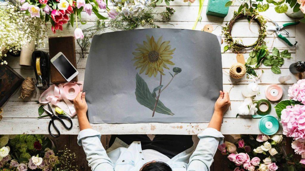 En kvinna håller upp en målad bild av en solros. Under bilden syns ett bord och vackra blommor.
